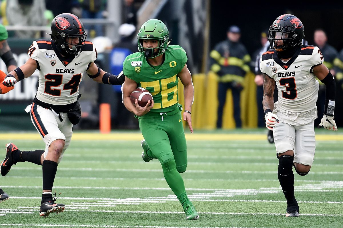 Running back Travis Dye of the Oregon Ducks runs with the ball as defensive back David Morris and defensive back Jaydon Grant of the Oregon State Beavers give chase during the first half of the game at Autzen Stadium on November 30, 2019 in Eugene, Oregon.