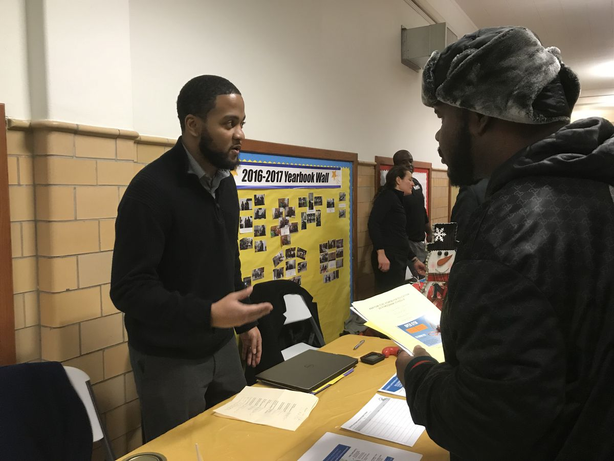 A representative of a community organization talks to those attending an event to announce the creation of family hubs in the Detroit school district.