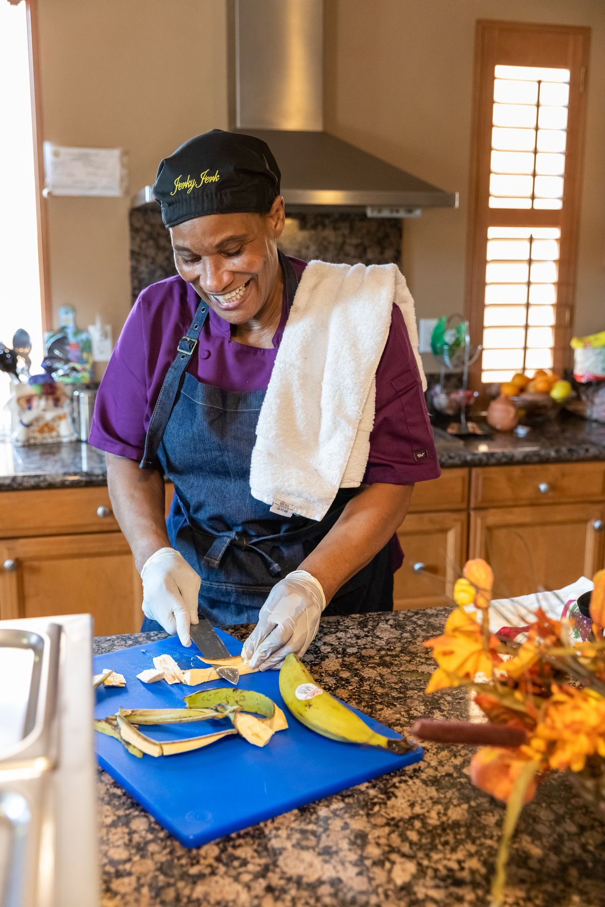 Evon McMurray slices plantains at her home kitchen restaurant Jerky Jerk with a blue cutting board and granite countertops.