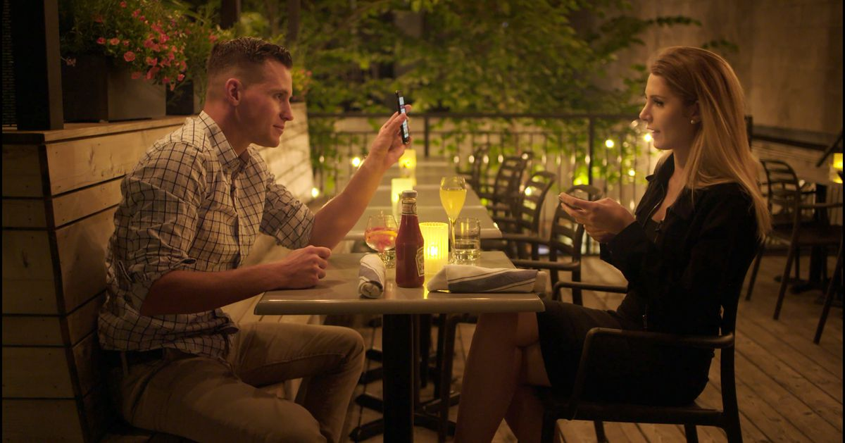 A man and a woman sitting across from each other in a restaurant.