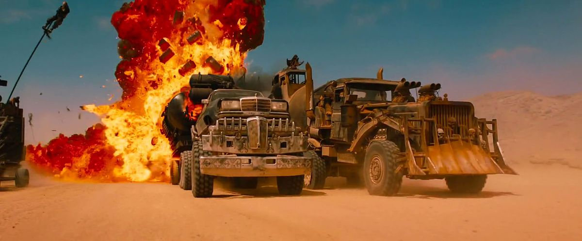two rusty brown trucks pimped out with post-apocalyptic guns collide in a ball of fire
