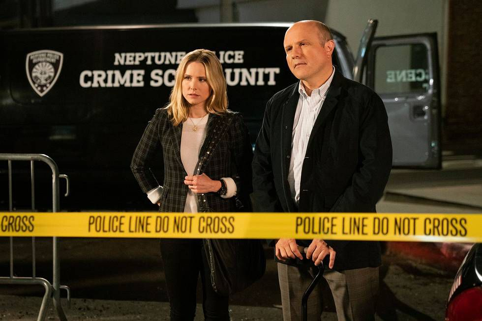 """Kristen Bell as Veronica Mars and Enrico Colantoni as Keith Mars stand in front of a crime scene tape that reads """"Police line do not cross."""" A Neptune police crime scene unit van is in the background."""