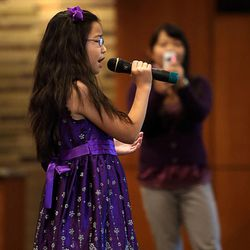 Carol Wang, 9, sings the national anthem as her mother, Sui Zhang, records her during tryouts at EnergySolutions Arena on Friday, Oct. 4, 2013. The winners will perform the anthem prior to each Utah Jazz home game during the 2013-2014 season.