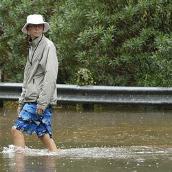 Haden Barber walks through the water near his home during Tropical Storm Harvey in Houston on Tuesday, Aug. 29, 2017.