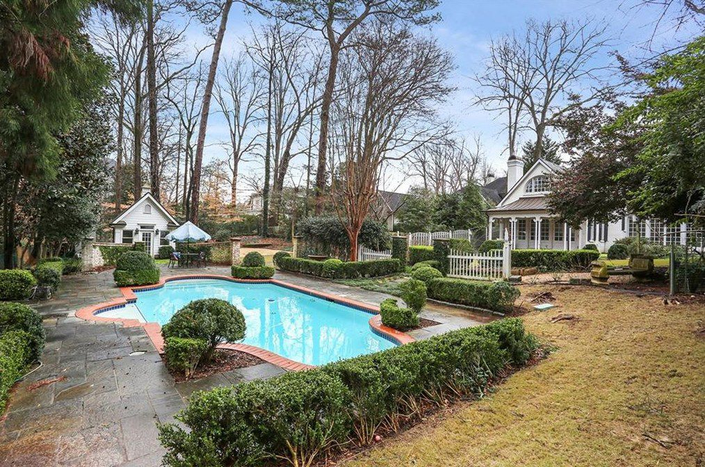 A heated pool in a backyard with many bushes and trees.