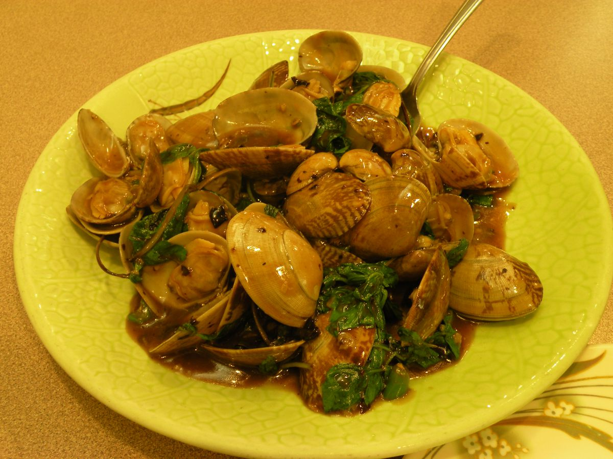 A yellow plate is covered with cooked clams and greens