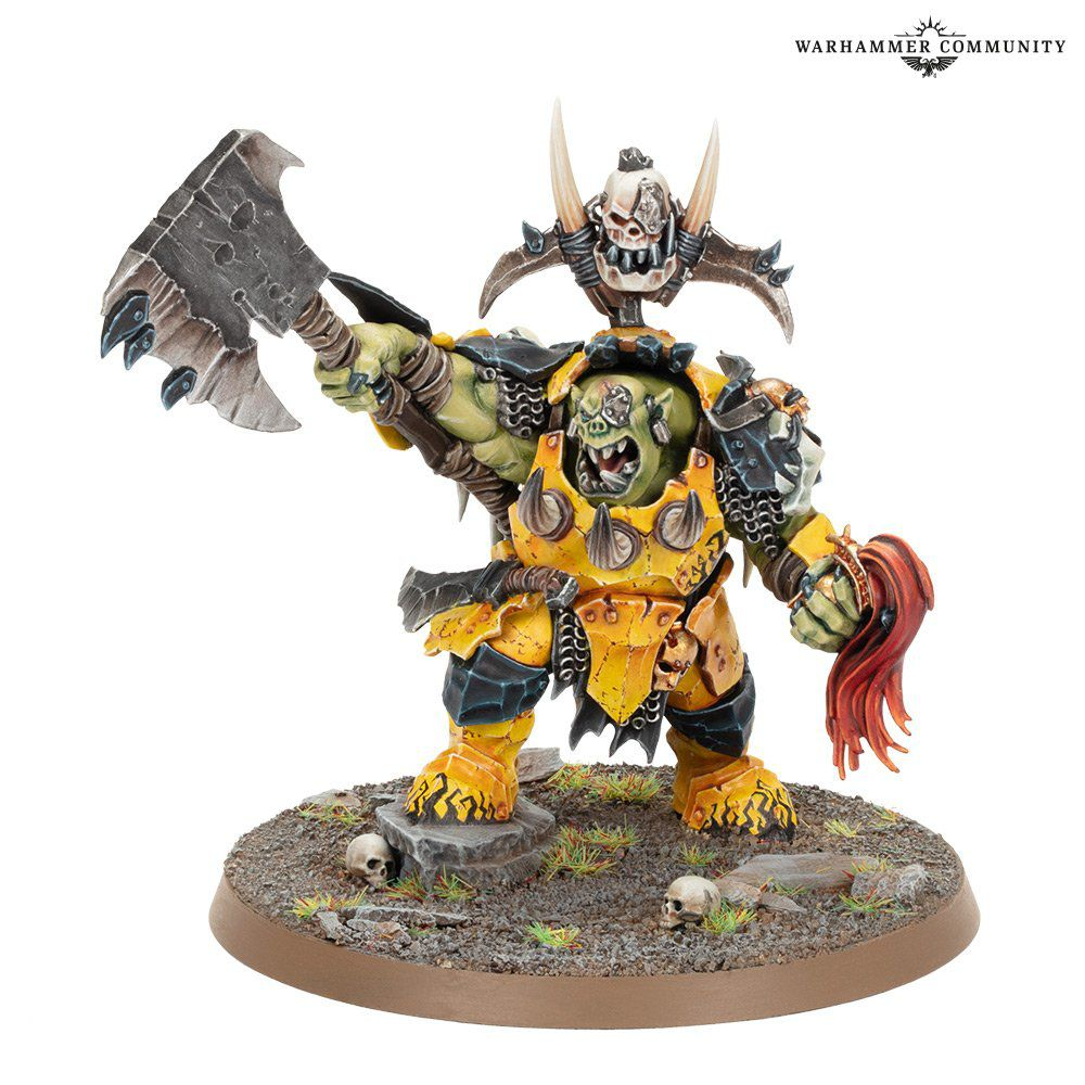 Warhammer Fantasy - a growling orc lifts his axe and menaces enemies while holding the helmet of one of Sigmar's warriors.