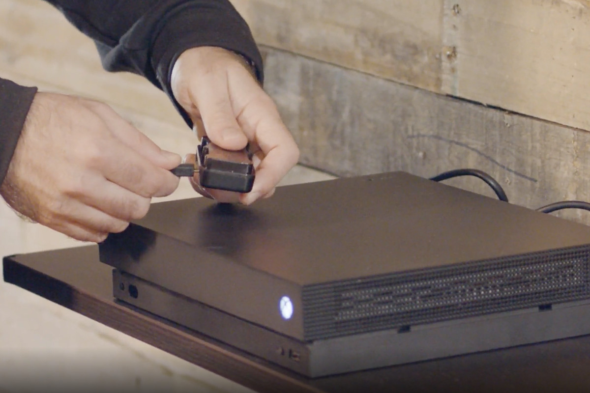 two hands hold a small dongle over an Xbox One X console