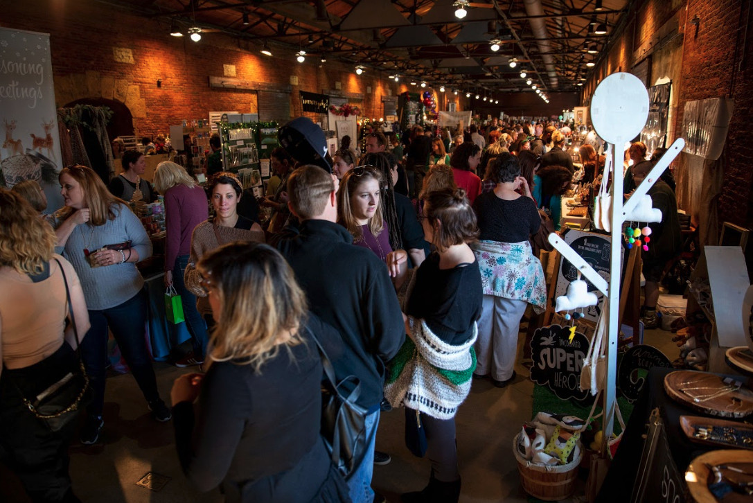 Crowd shopping for gifts during a holiday market.
