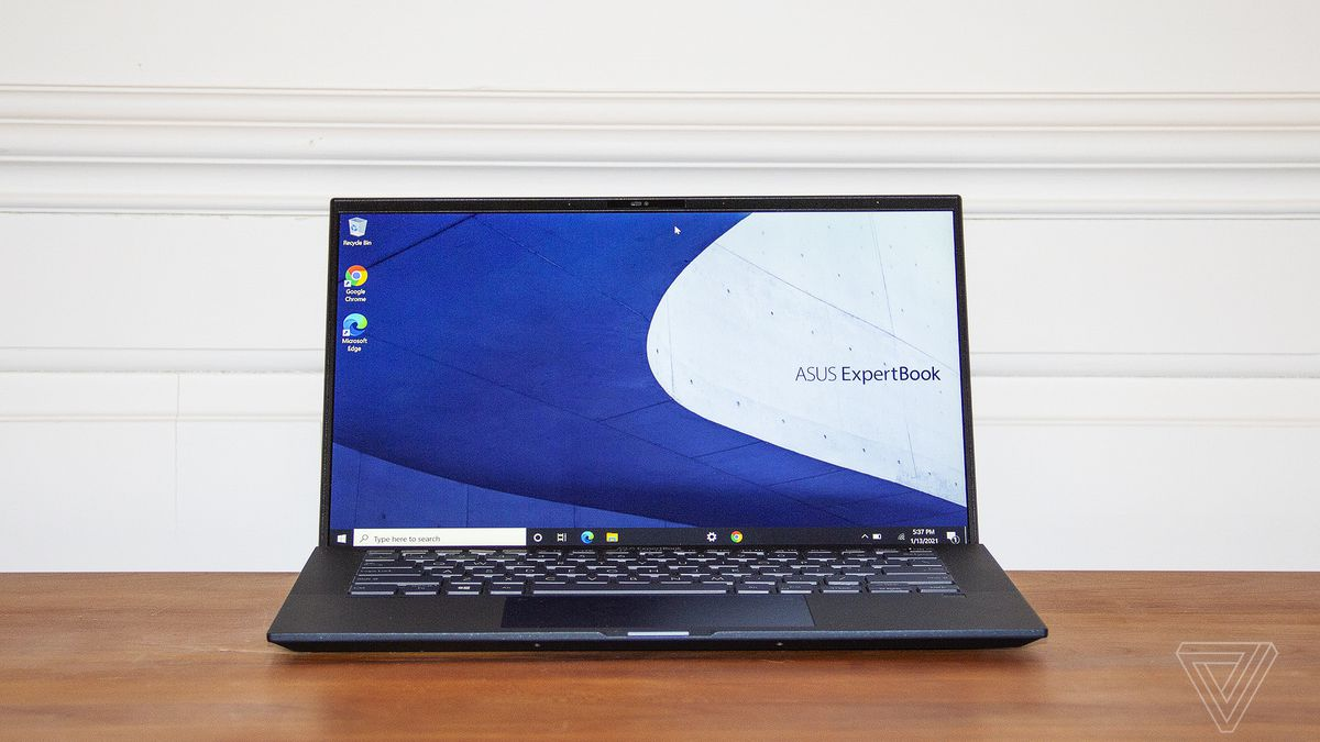 The Asus Expertbook B9450 sits open. The screen displays the ExpertBook logo on a white and blue background.
