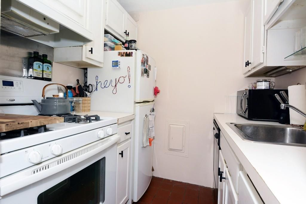 A narrow kitchen with a fridge at one end, against the wall.
