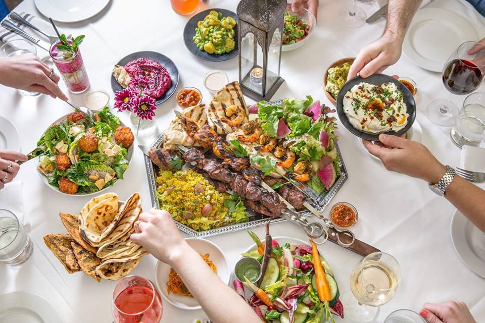 A white table full of salad, spreads, pita, and skewered meat