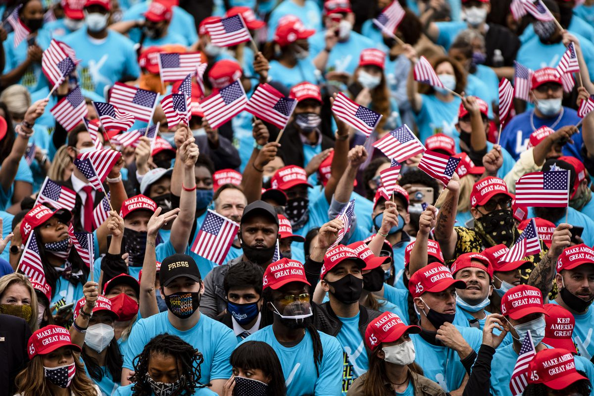 """A mass of people, all in cobalt blue shirts reading """"We the free,"""" with the Blexit logo (a white stick figure with a round head). Nearly all of them have on red hats, with Make America Great Again stitched in white. Many wave flags. About half have on masks; the other half have their masks pulled down onto their chins."""