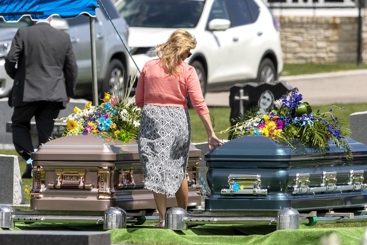 Kathy Butterfield walks between the caskets of her son, Tony Butterfield, and daughter-in-law, Katherine Butterfield, after the families gathered in the Herriman City Cemetery for graveside services on Saturday, April 25, 2020. The couple was shot and killed at their home in West Jordan on Saturday, April 18, 2020. Albert Enoch Johnson was arrested the following Wednesday in Stockton, California, in connection to the Butterfields' shooting deaths.