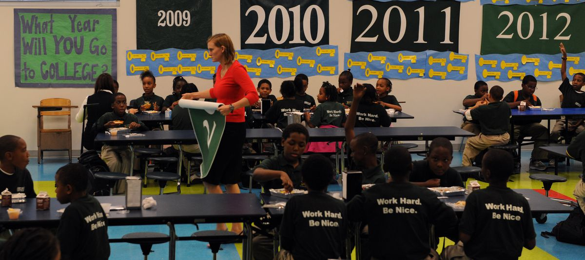 Sarah Hayes, principal, crosses the cafeteria during lunch at KIPP DC Public Charter School in Washington, DC in 2008. Banners listing the year students will enter college line the cafeteria. (Photo by Jahi Chikwendiu/The Washington Post/Getty Images)
