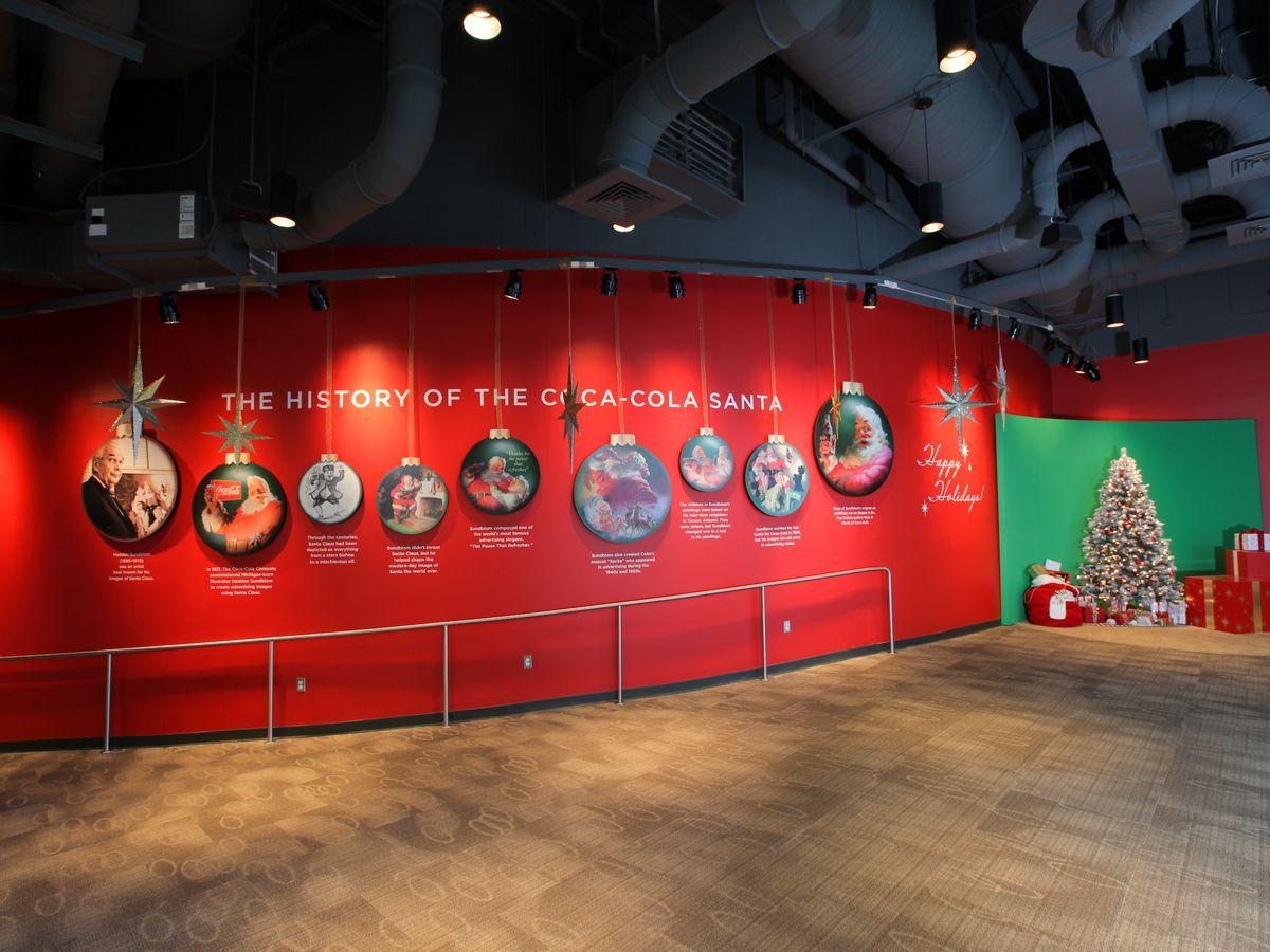 A red wall with various circular images of Santa.