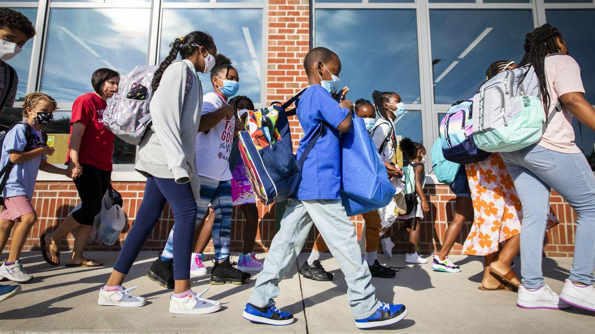 A crowd of elementary school kids walking on the sidewalk in front of their school building.