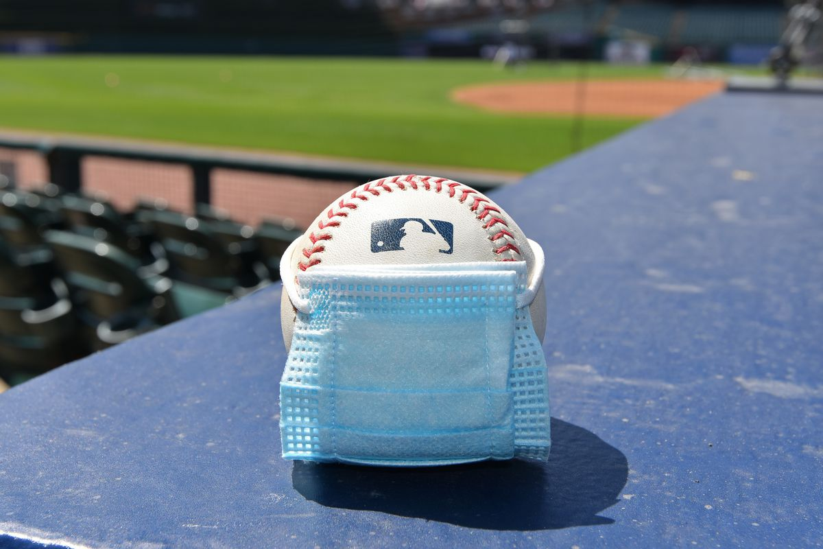 A detailed view of an official Major League Baseball with a surgical mask placed on it sitting on the dugout during the Detroit Tigers Summer Workouts at Comerica Park on July 5, 2020 in Detroit, Michigan.