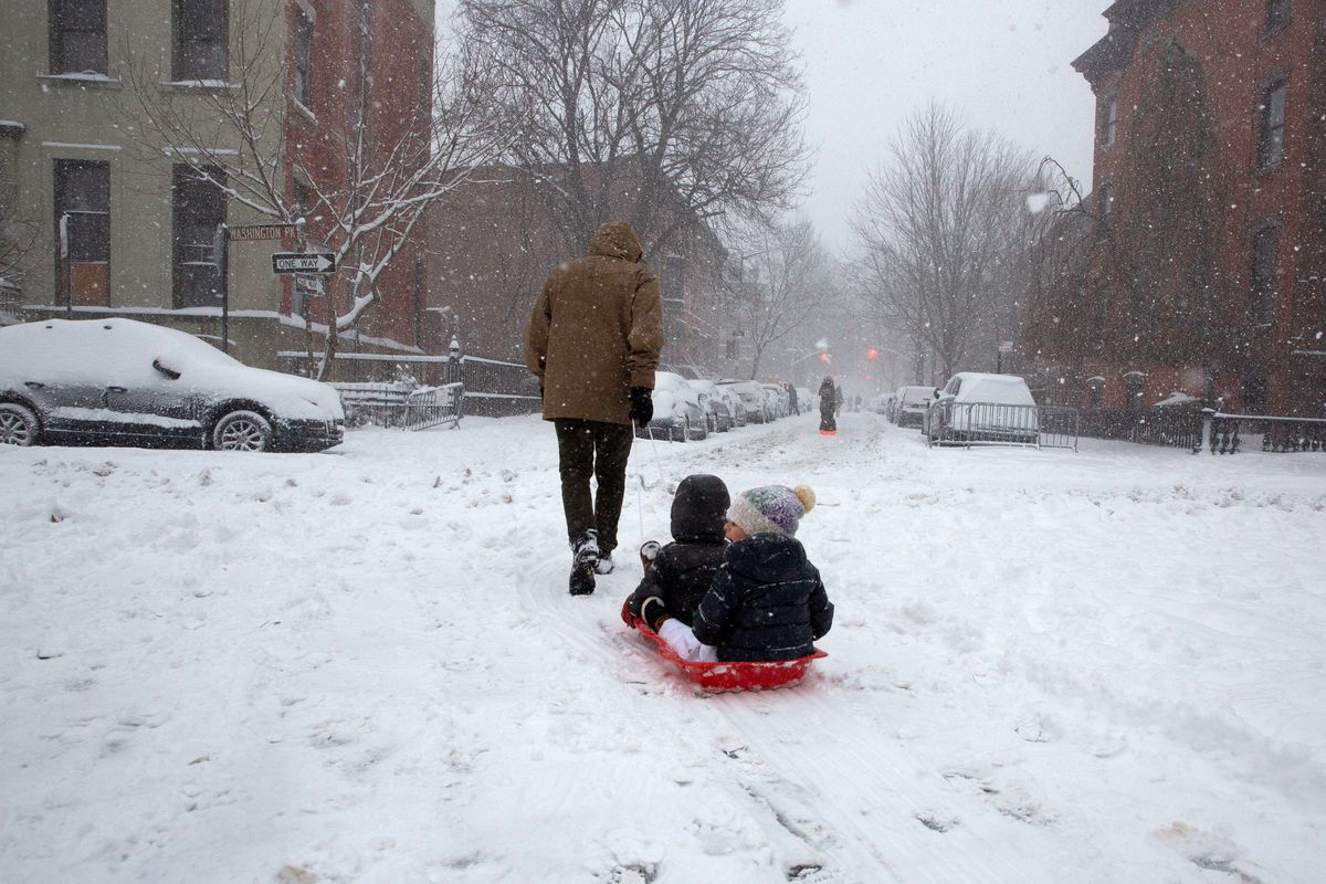 A parent helps his young ones enjoy a snow day in Fort Greene Park, Feb. 1, 2021.