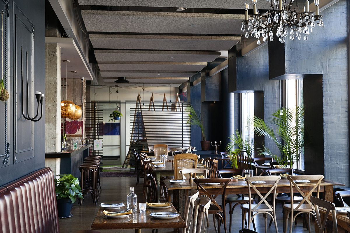The open front dining room with farmhouse chairs, wood tables, blue walls, all set for service