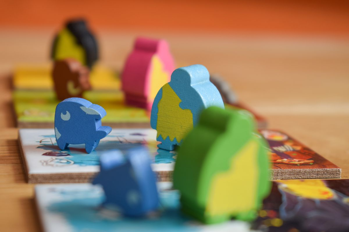 A fish and a cave person meeple, in blue, stand on a set of Kingdomino Origins tiles ready to be played to the table.