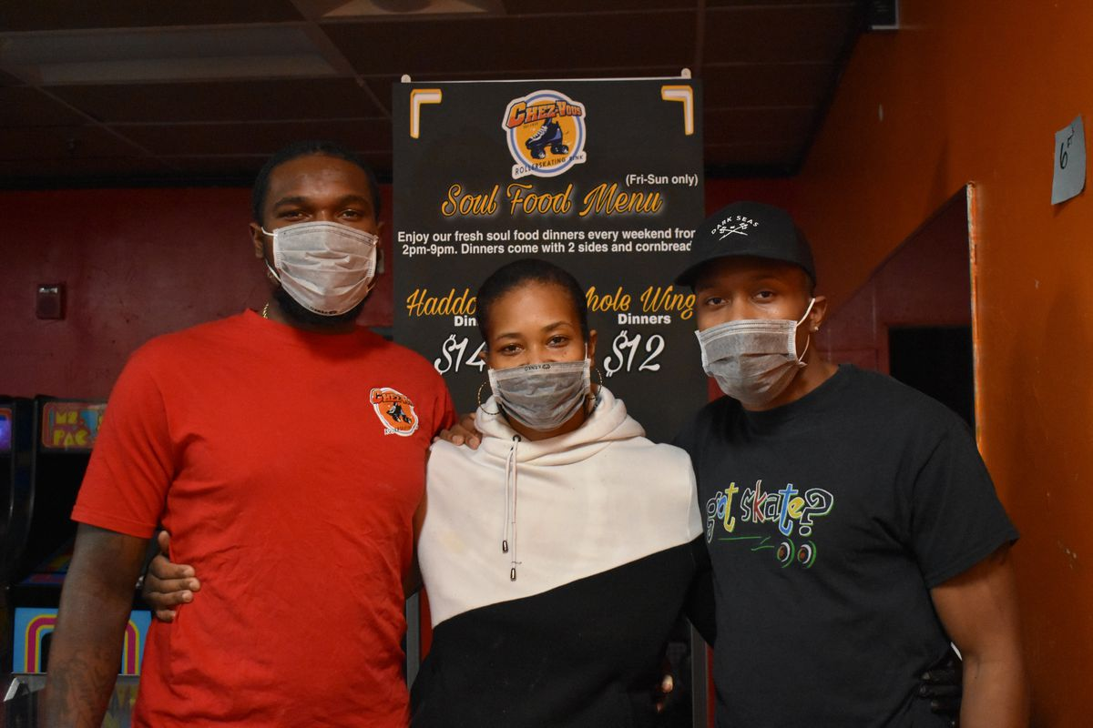 Edward Toney Jr., Tarsha Foster-Toney, and Derick Foster-Toney — the owners of Chez-Vous roller skating rink — standing near the entryway