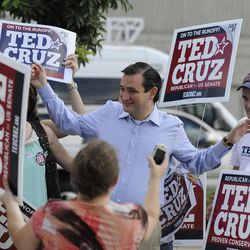Former Texas Solicitor General Ted Cruz, center, greets supporters at a voting precinct Tuesday, July 31, 2012, in Houston. Cruz faces Lt. Gov. David Dewhurst in the Republican primary runoff election for the Republican nomination for the U.S. Senate.