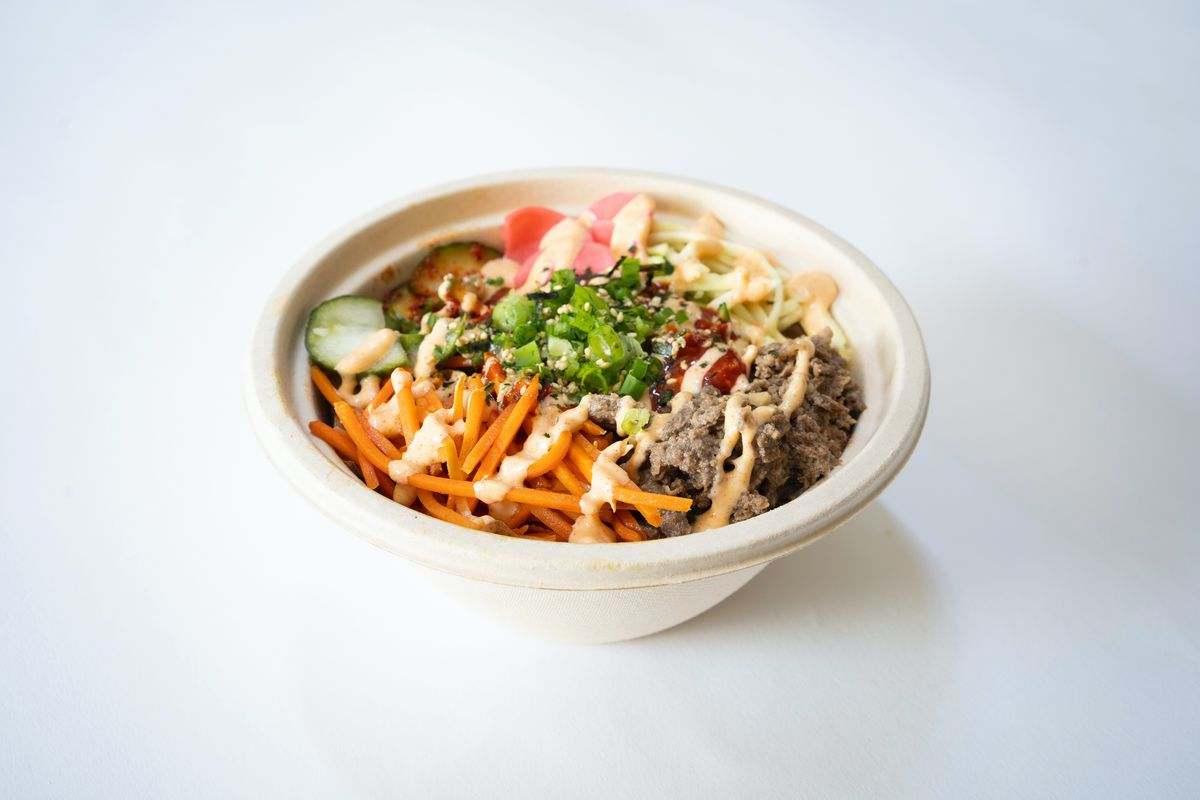 A compostable bowl isolated on a white background. The bowl is full of beef bulgogi bibimbap, with matchstick carrots, cucumbers, a zigzag of aioli, and other ingredients.
