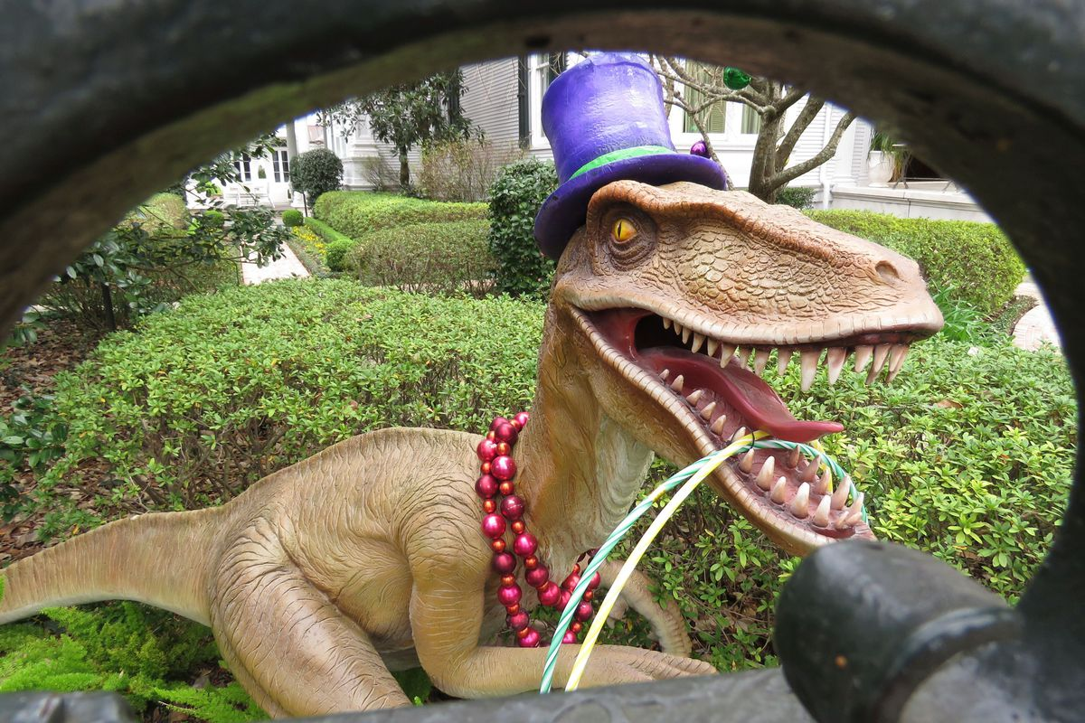 A top-hatted dinosaur, shown Tuesday, Jan. 26, 2021, is among Mardi Gras decorations in the yard of a mansion on St. Charles Avenue in New Orleans.