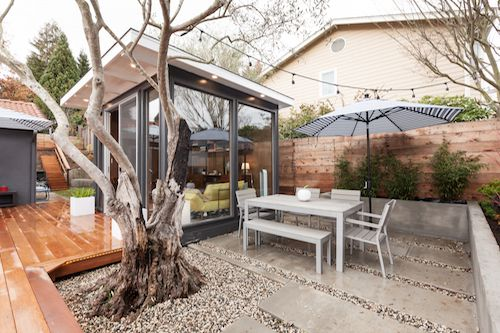 An outdoor area with chairs, a table, and an umbrella.
