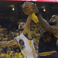 Cleveland Cavaliers forward LeBron James (23) grabs a rebound against Golden State Warriors guard Stephen Curry (30) during the first half of Game 1 of basketball's NBA Finals in Oakland, Calif., Thursday, June 1, 2017.