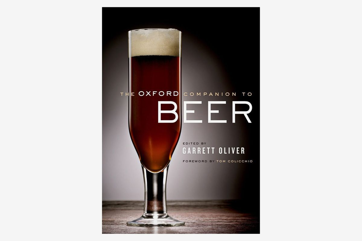 "The cover of ""The Oxford Companion to Beer"" with a glass of beer on a dark background"