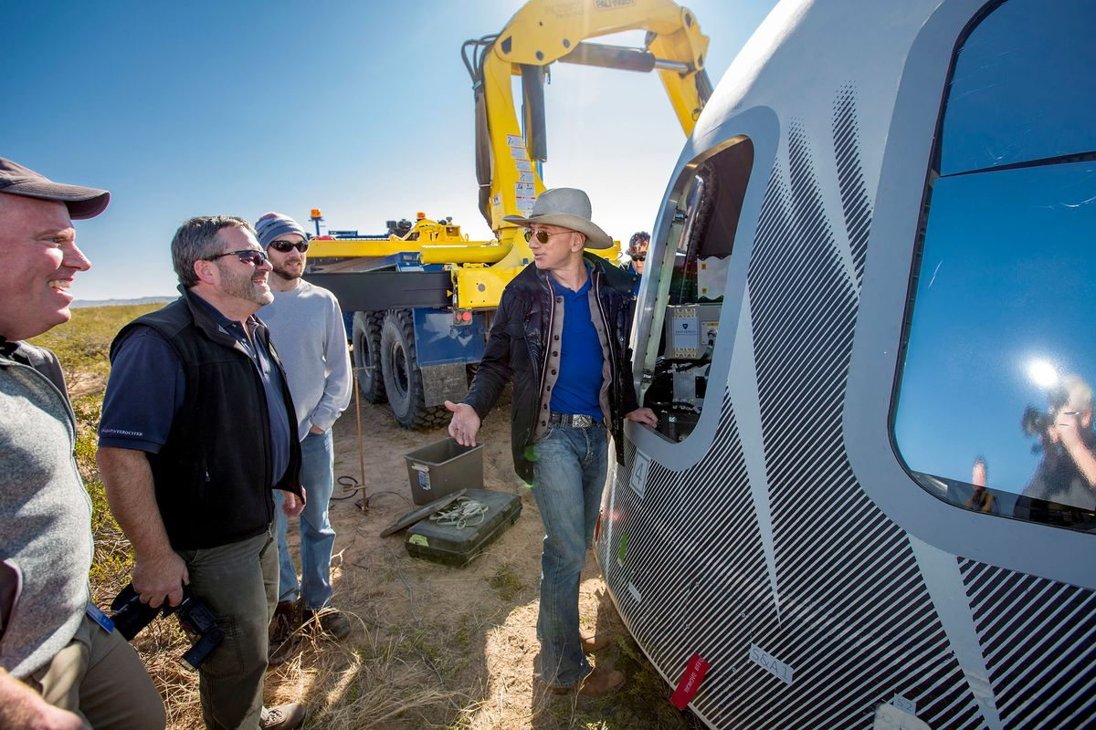 Jeff Bezos, right, the world's richest man and founder of aerospace company Blue Origin, checks out the company's Crew Capsule 2.0 after a test flight on Dec. 12, 2017. Bezos plans to launch into space aboard Blue Origin's New Shepard rocket later this month.