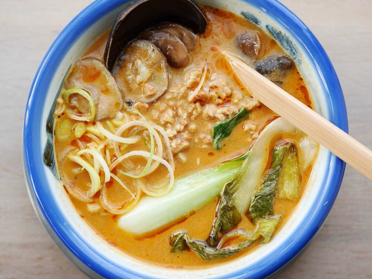 A photo of vegan hazelnut tantanmen at Afuri, with pieces of floating greens, hunks of mushroom, and swirls of onion