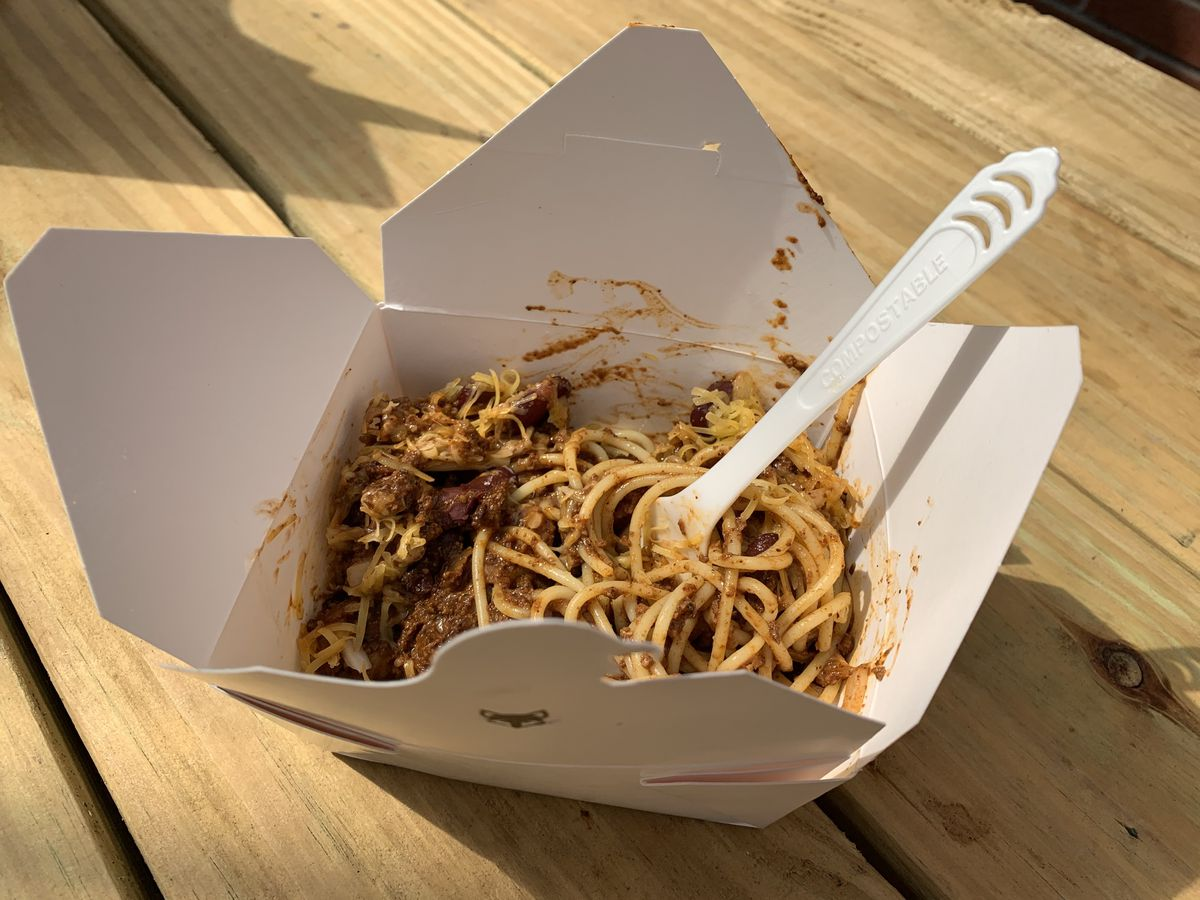 A takeout box filled with noodles in chili sits on a wooden table with a fork in it.