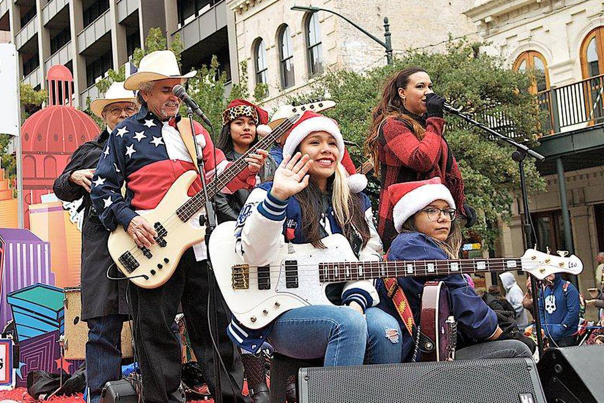 Band in matching Texas flag shirts with guitars, accordion on parade float