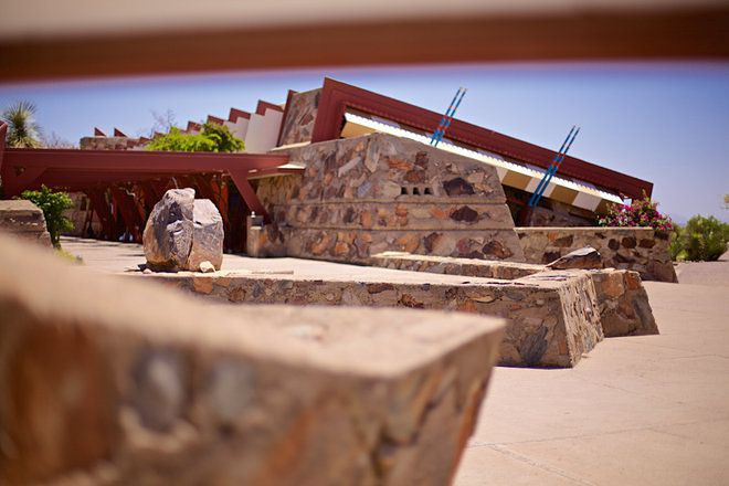 Taliesin West by Frank Lloyd Wright. The exterior is stone with a red sloping roof. The house is surrounded by desert.