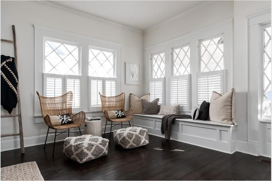 A set of windows and bench seating beside a white door.
