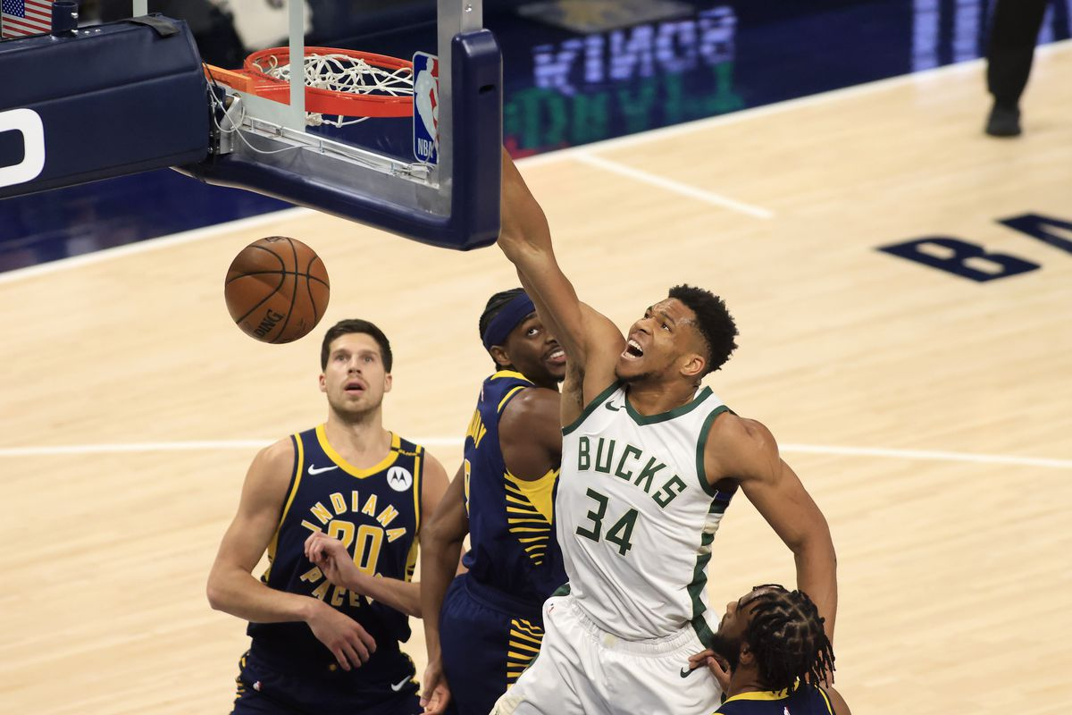 Giannis Antetokounmpo #34 of the Milwaukee Bucks dunks the ball over Justin Holiday #8 of the Indiana Pacers during the first quarter at Bankers Life Fieldhouse on May 13, 2021 in Indianapolis, Indiana.