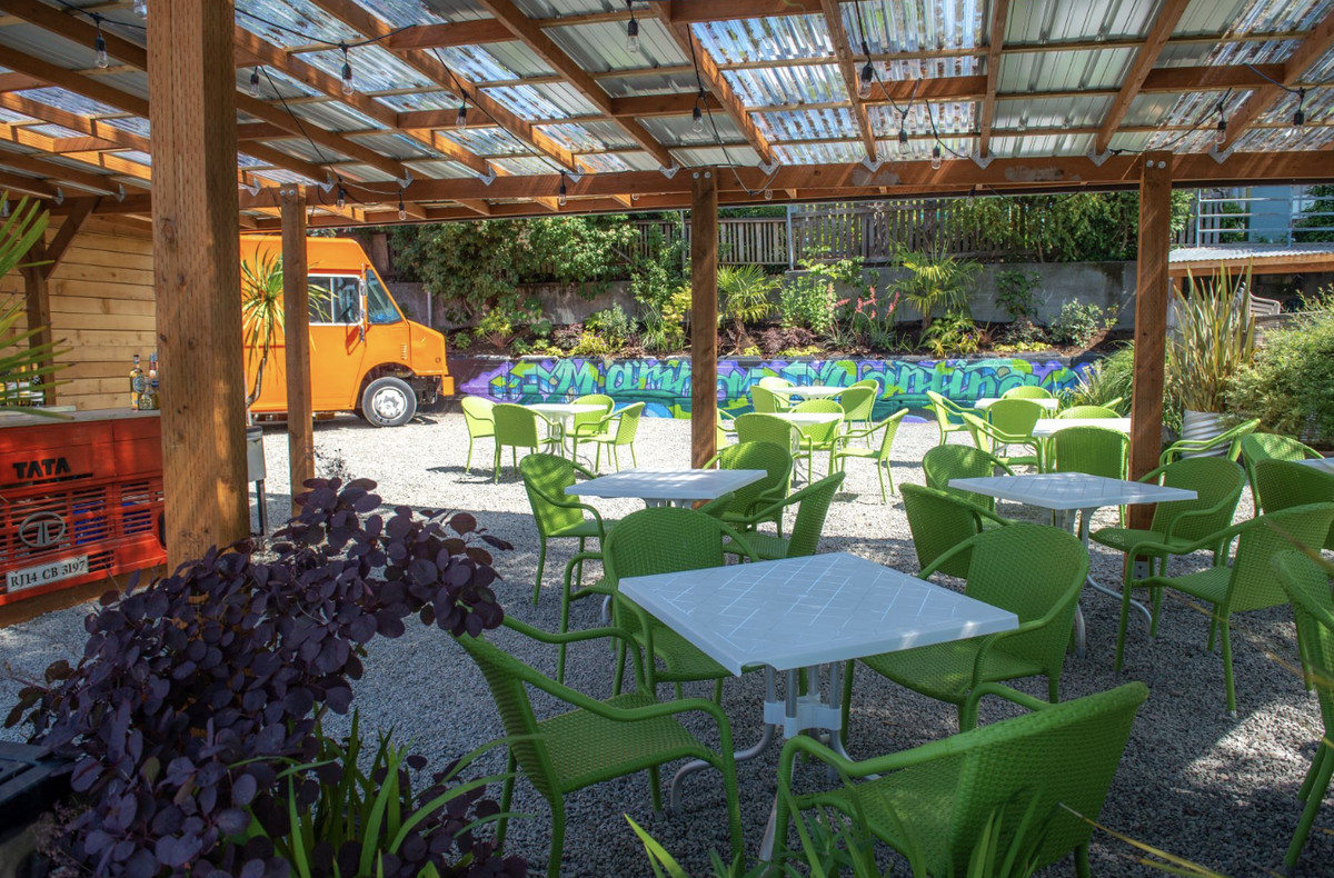 The downstairs patio at Agua Verde, with a bright orange food truck in the background.