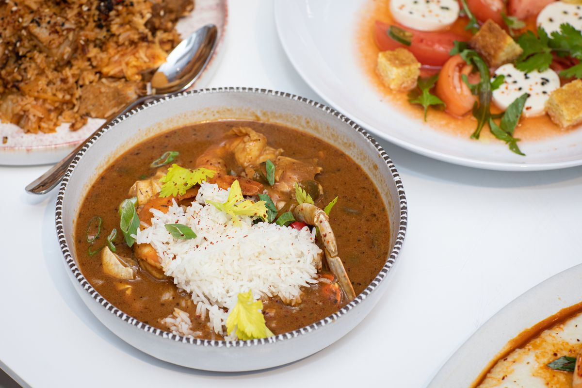 A bowl of gumbo with white rice and a shrimp tail sticking out