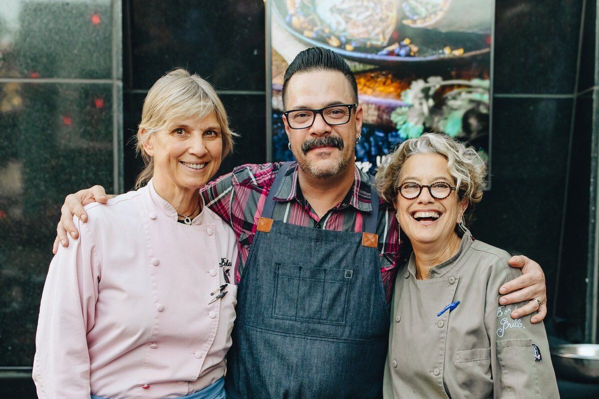 Two women chefs stand beside a male chef