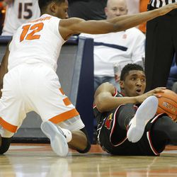 Louisville's Donovan Mitchell, right, grabs a loose ball from Syracuse's Taurean Thompson, left, in the first half of an NCAA college basketball game in Syracuse, N.Y., Monday, Feb. 13, 2017. (AP Photo/Nick Lisi)