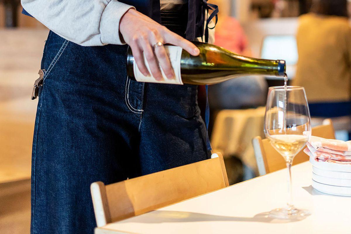 Kismet wine director Kae Whalen pours white wine into a glass.