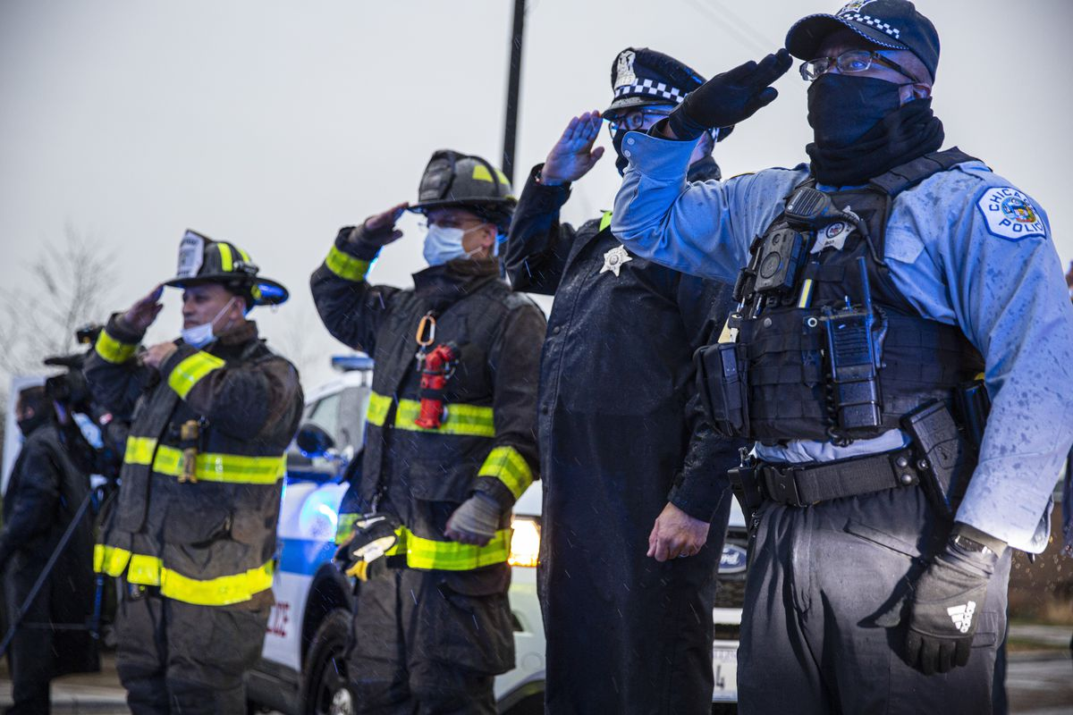 Police and firefighters salute a procession at the Cook County medical examiner's office at 2121 W. Harrison St., Tuesday, Nov. 24, 2020.