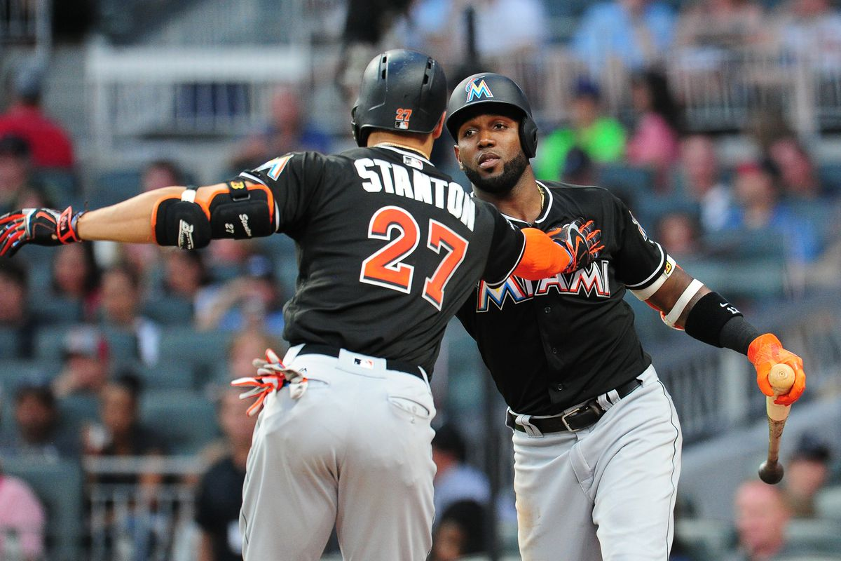ATLANTA, GA - AUGUST 5: Giancarlo Stanton #27 of the Miami Marlins is congratulated by Marcel Ozuna #13 after hitting a sixth inning solo home run against the Atlanta Braves at SunTrust Park on August 5, 2017 in Atlanta, Georgia. (Photo by Scott Cunningham/Getty Images)