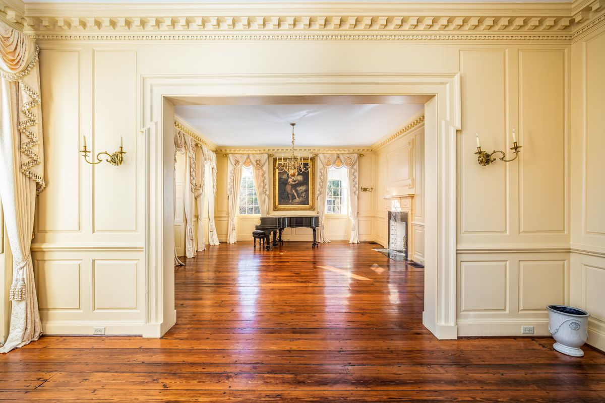 An open ballroom features a grand piano on one end and wooden floors.