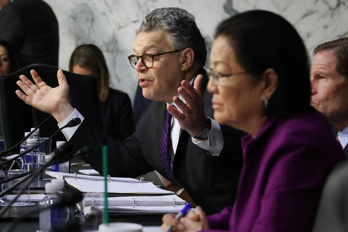 Sen. Al Franken holds out his hands while questioning tech executives at a congressional hearing.