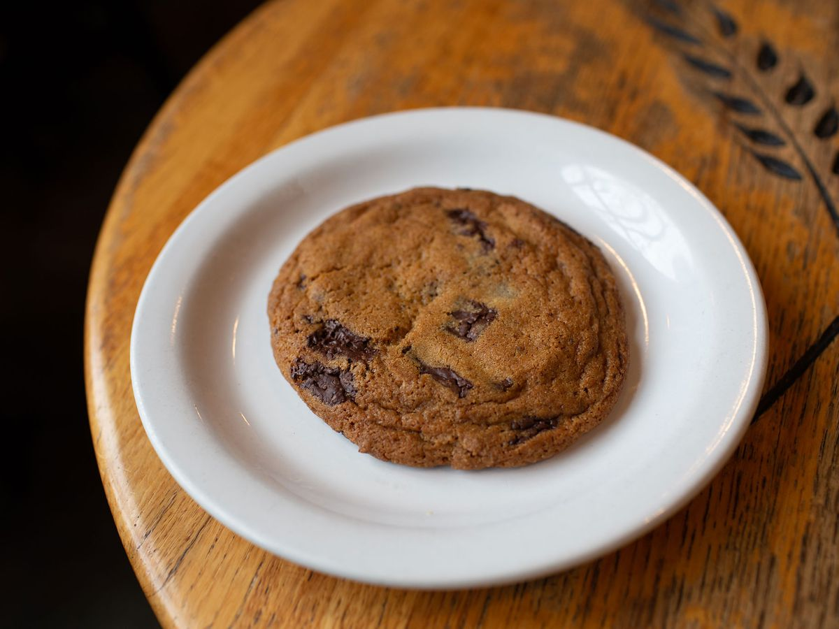 A latte-brown cookie with rings of wrinkles, with a handful of chocolate chunks, sits on a white plate at Ken's Artisan Bakery