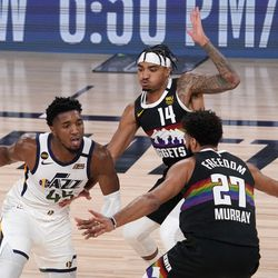 Utah Jazz's Donovan Mitchell (45) looks for an opening against the defense of Denver Nuggets' Gary Harris (14) and Jamal Murray (27) during the second half an NBA first round playoff basketball game, Tuesday, Sept. 1, 2020, in Lake Buena Vista, Fla.